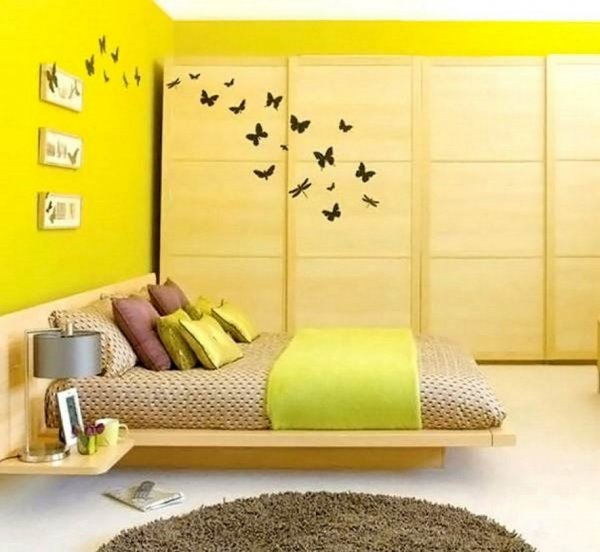 sunny-yellow-wall-bedroom-decoraation-with-wooden-bed-platform-and-wooden-cabinet-915x843